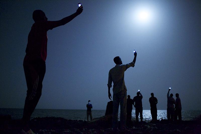 Migranten suchen an der Küste von Djibuti nach Empfang für ihr Handy.