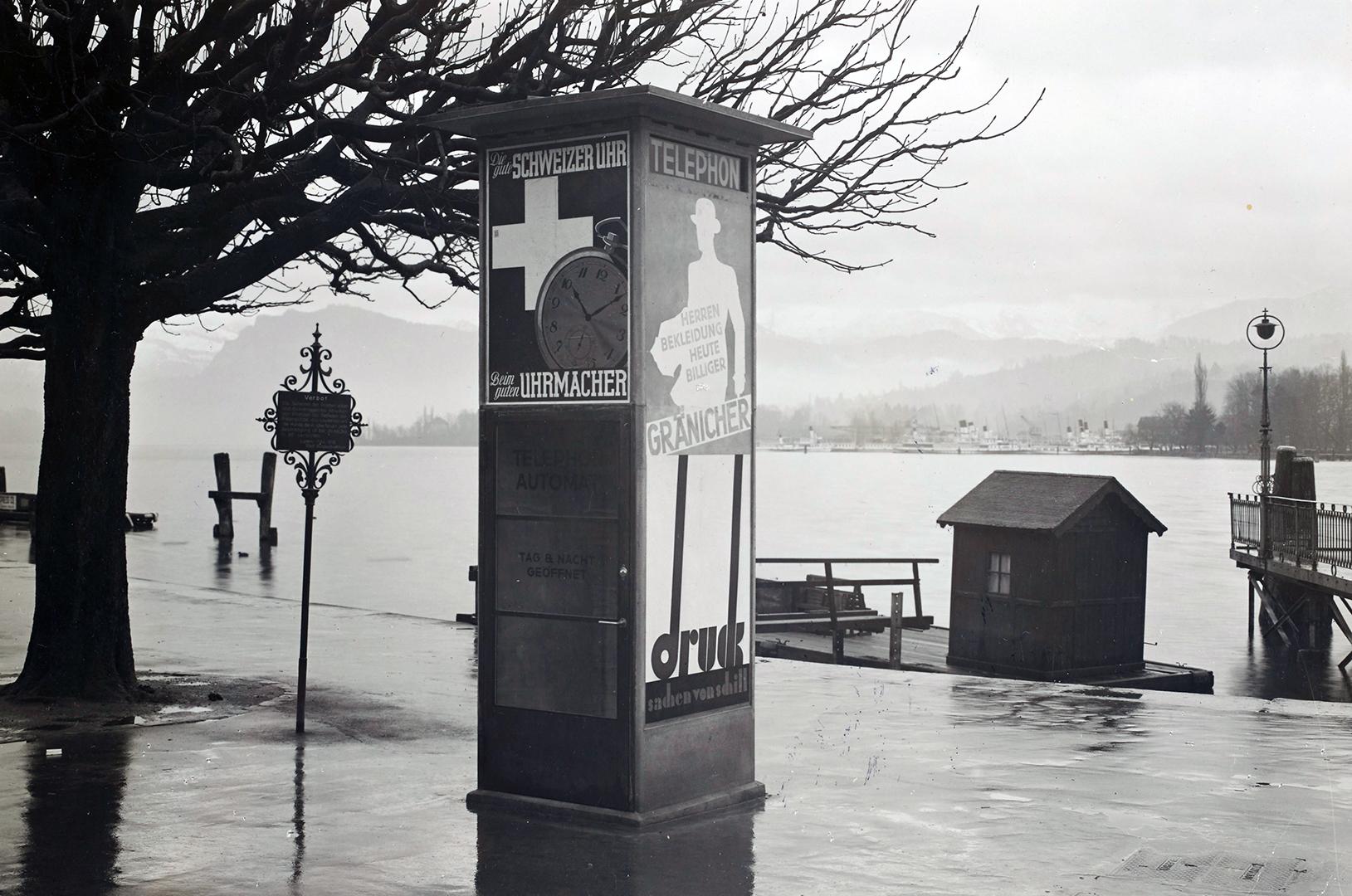 Litfasssäule mit Telefonkabine an der Seepromenade in Luzern. Aufnahme von ca. 1932.