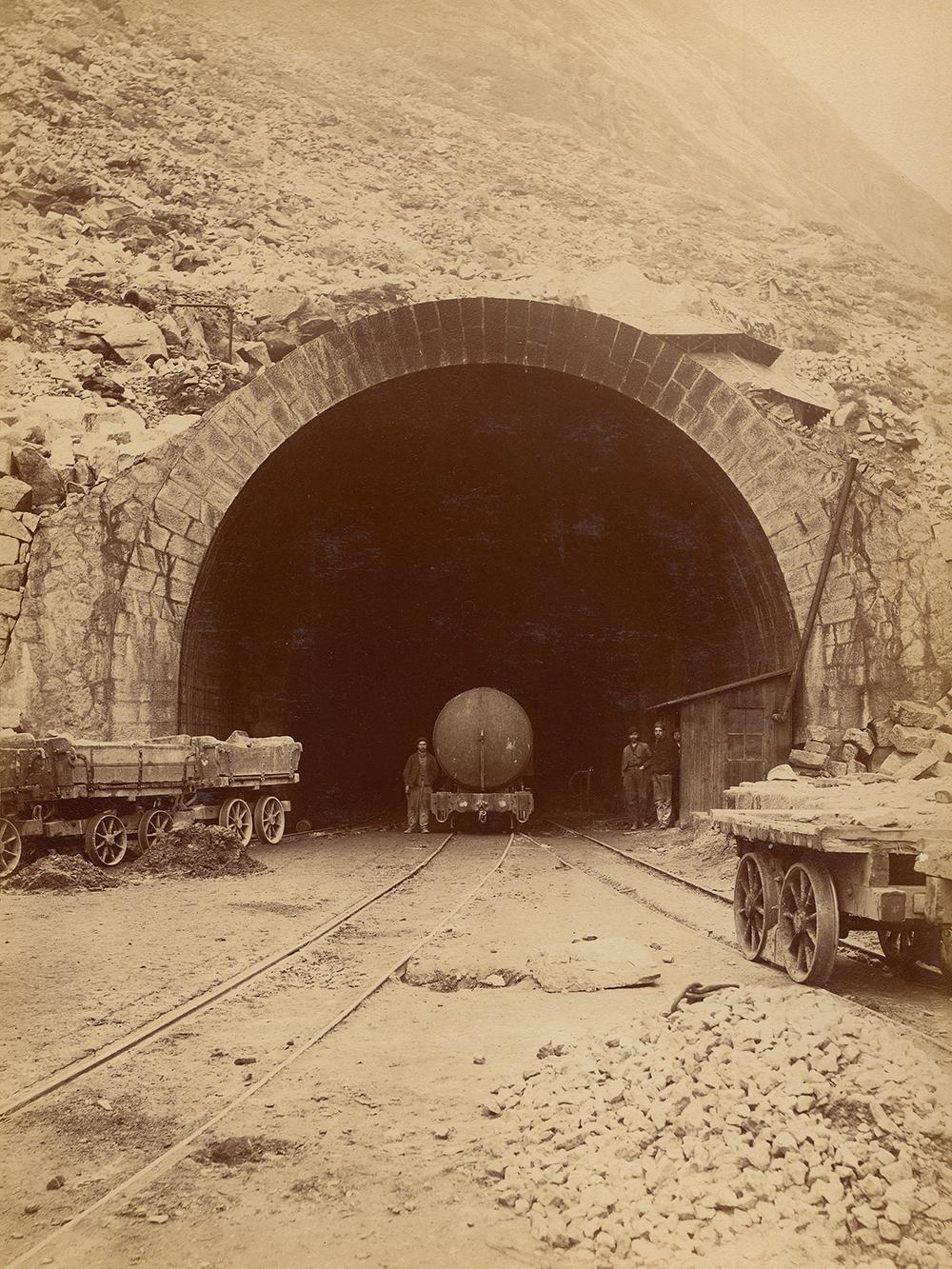 Photographie de l'entrée du Gothard, vers 1875. On reconnaît aisément les trois hommes posant contre le mur et au niveau du wagon.