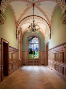 Le vestiaire du Conseil des États, au Parlement à Berne, après la rénovation de 2006-2008. En arrière-plan, le vitrail de Christian Baumgartner datant de 1902.