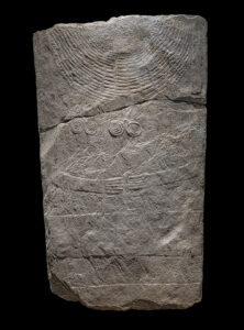 """Human-shaped stela """"Don Bosco 2"""" with arms and hands, broad belt and neck ornament with double spiral pendants. Marble. 3,000–2,500 BC. Switzerland, Canton of Valais, Sion."""