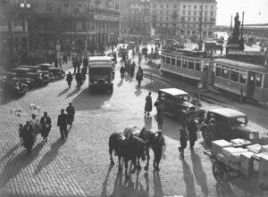 Autos, Pferde und (elektrische) Trams drängen sich auf dem Bahnhofplatz in Zürich, um 1930.
