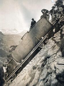 Für den Bau des Wasserkraftwerks im Ackersand, Wallis wird eine Druckröhre den Berg hochgeschafft, um 1922.