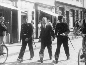 Two policemen escort Hans Vollenweider to his trial.