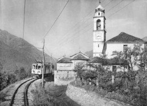 Der Elektrotriebwagen BCFe 4/4, Nr. 18, der Centovalli-Bahn passiert am 24.8.1925 die Pfarrkirche von Tegna.