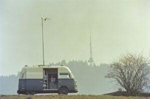 Ein Peilwagen der PTT vor dem Bantiger Sendeturm im Jahr 1976. Der Turm prägt die Silhouette des Hügels markant.
