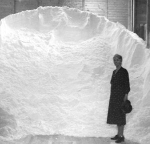 Frau vor einem Salz-Haufen in Schweizerhalle, 1950.