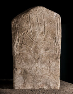 Male stela with necklace, hatchets, daggers, battle ax and multi-row belt. Limestone. 3,000-2,500 BC. Italy, Trentino-Alto Adige, Arco.