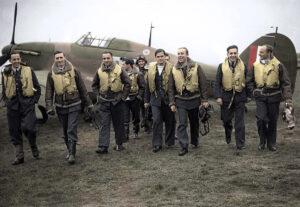 Pilotes du 303e escadrille de la Royal Air Force. Jan Zumbach se tient à l'arrière-plan et porte des lunettes d'aviateur sur la tête. Photo couleur, vers 1940.