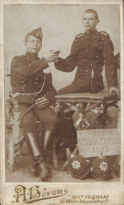 Zwei Soldaten verewigen ihre Abreise in die niederländischen Kolonien auf einer Porträtkarte, 1895.