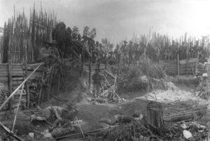 Soldaten der niederländischen Kolonialarmee posieren vor getöteten Dorfbewohnerinnen und Dorfbewohnern in Kuta Reh, Sumatra.